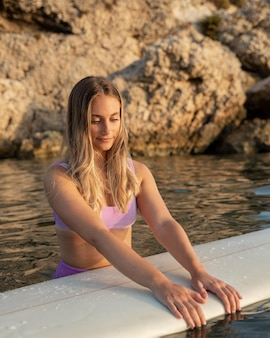 Front view of beautiful woman with a surfboard