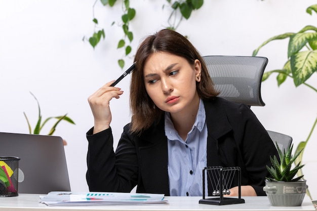 A front view beautiful young businesswoman in black jacket and blue shirt thinking in front of table business job office