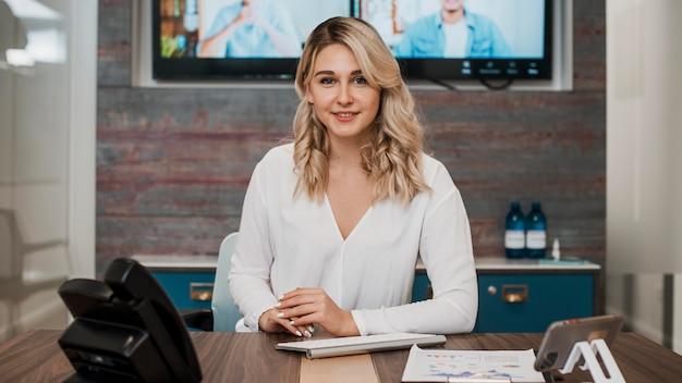 Вид спереди красивая молодая женщина в офисе