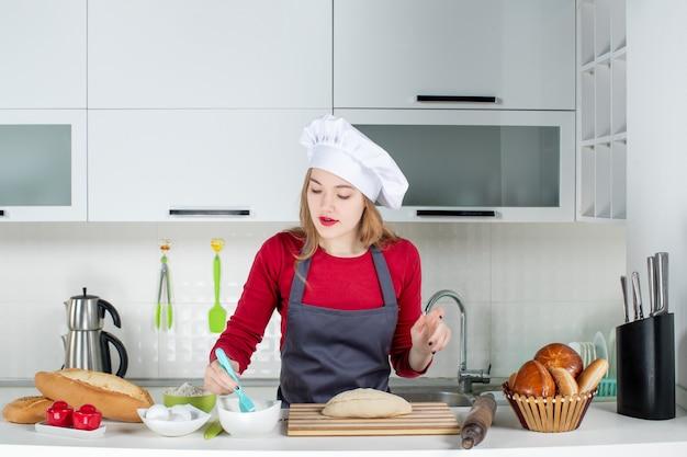 正面図キッチンでクック帽子とエプロン泡立て器の卵の美しい若い女性