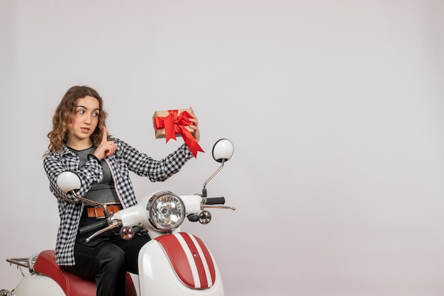 Front view of beautiful young woman on moped holding gift on grey wall