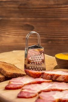Fette di becon vista frontale su tagliere per pane grattugia su superficie di legno