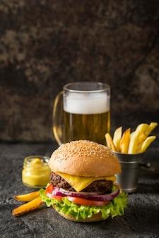 Hamburger di manzo vista frontale, patatine fritte e salsa con birra e copia-spazio