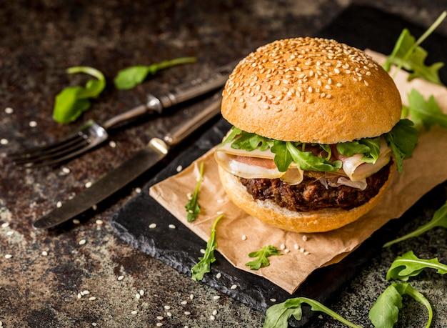 Hamburger di manzo vista frontale con pancetta e posate