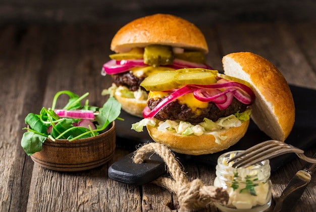Гамбургеры из говядины с солеными огурцами и красным луком на разделочной доске, вид спереди