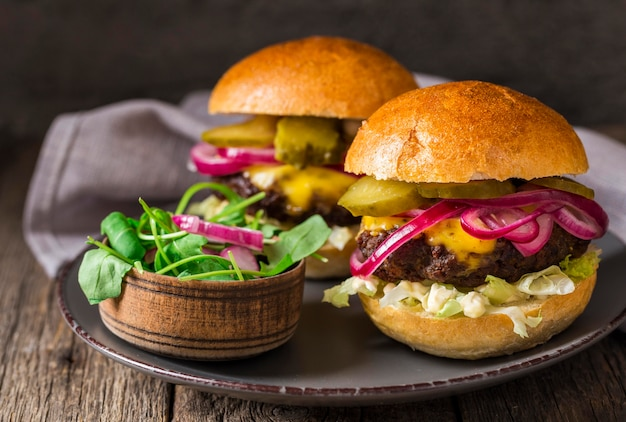 Front view beef burgers with pickles on cutting board