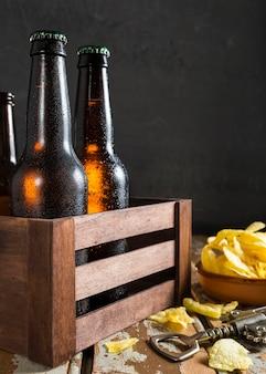 Vista frontale delle bottiglie di vetro di birra in cassa con patatine