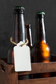 Vista frontale delle bottiglie di vetro di birra in cassa con etichetta