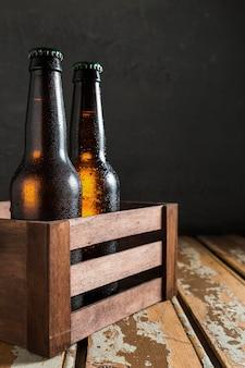 Vista frontale delle bottiglie di vetro di birra in cassa