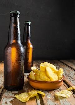 Vista frontale delle bottiglie di vetro di birra con patatine