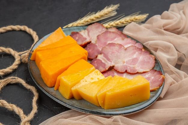 Vista frontale dei migliori snack deliziosi per il vino su un asciugamano su un tavolo scuro