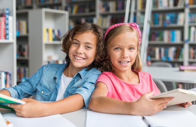 Лучшие друзья, вид спереди, вместе делают домашнее задание в библиотеке