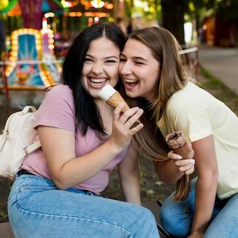Лучшие друзья, вид спереди, вместе едят мороженое
