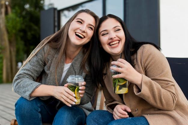 Лучшие друзья, вид спереди, наслаждаются коктейлями