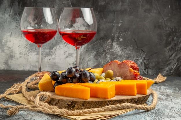Vista frontale del miglior spuntino con vari frutti e cibi su un vassoio in legno marrone corda e due bicchieri di vino rosso su un vecchio giornale