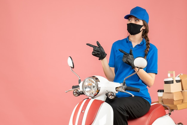 Front view of bewildered courier girl wearing medical mask and gloves sitting on scooter delivering orders on pastel peach background