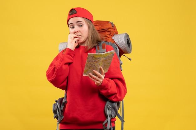 旅行マップを保持している正面図当惑した女性のバックパッカー