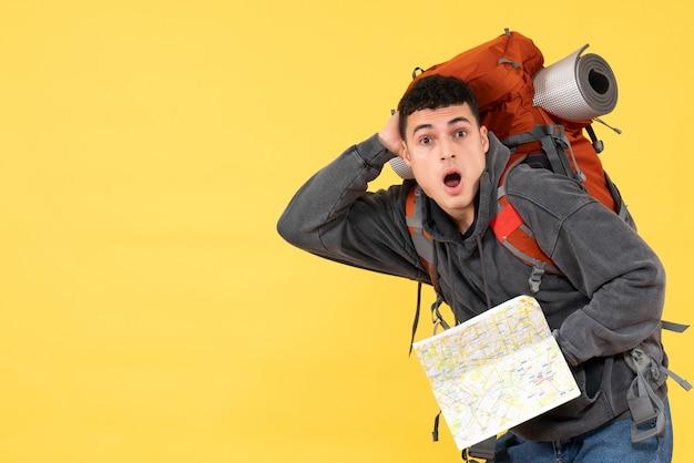 Vista frontale uomo sconcertato viaggiatore con zaino rosso che tiene mappa