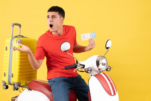 Front view bewildered young male in casual clothes on moped holding ticket