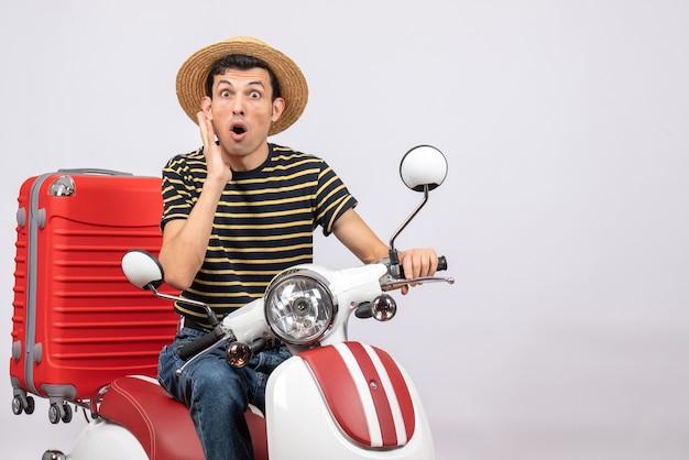 Vista frontale del giovane sconcertato con cappello di paglia sul ciclomotore