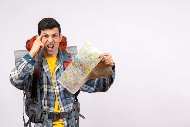 Вид спереди сбитый с толку молодой путешественник с рюкзаком, держащим карту
