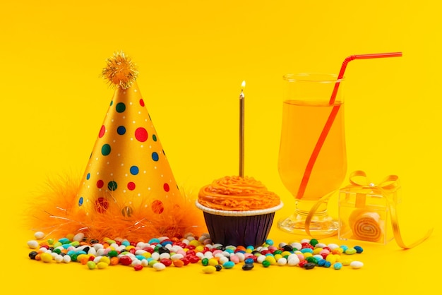 A front view birhtday cake with candle along with colorful candies and birthday cap on yellow, color sweet biscuit