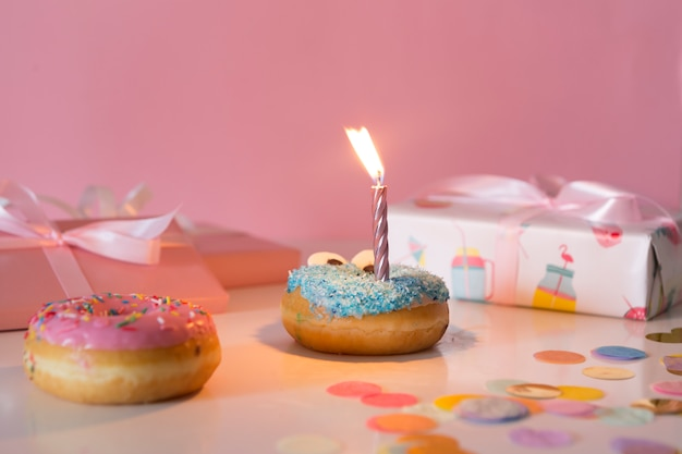 Front view birthday donut with lit candle