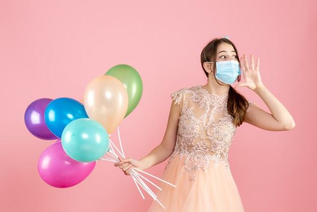 カラフルな風船を持って何かを聞いている医療マスクを持つ正面図の誕生日の女の子