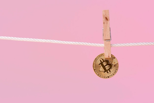 Front view of bitcoin held by clothing pin on rope