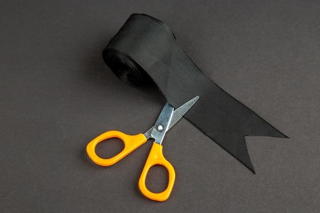 Vista frontale fiocco nero con le forbici sulla superficie scura colore tenebre vestiti cucito a maglia