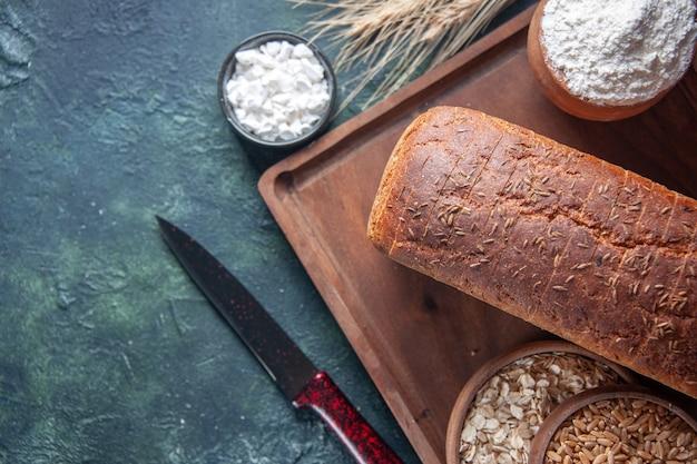 Vista frontale di farina di fette di pane nero in una ciotola su tavola di legno e punte di coltello farina d'avena cruda di grano sul lato sinistro su sfondo invecchiato di colori misti