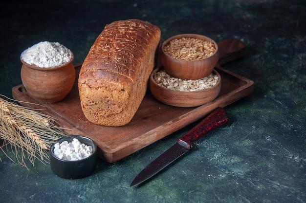 Vista frontale del pane nero fette di farina in una ciotola su tavola di legno e punte di coltello farina d'avena cruda di grano su colori misti sfondo in difficoltà