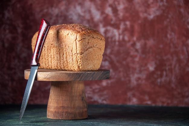 Vista frontale di fette di pane nero su tavola di legno e coltello sul lato destro su sfondo angosciato di colori misti