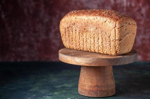 Vista frontale di fette di pane nero su tavola di legno su sfondo invecchiato di colori misti con spazio libero