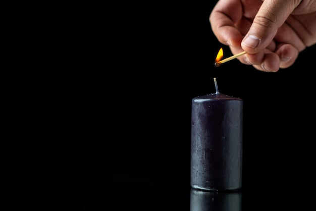 Front view of black candle on the dark surface