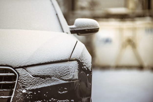 Front view of a black car covered with a thin layer of snow