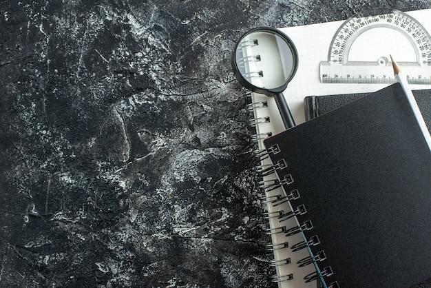 灰色の背景にペンと拡大鏡が付いた正面図の黒いコピーブックメモ帳大学の学校のレッスンカラーボードペンのコピーブック