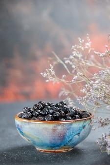 Ribes nero di vista frontale nella ciotola sul posto isolato della copia di superficie
