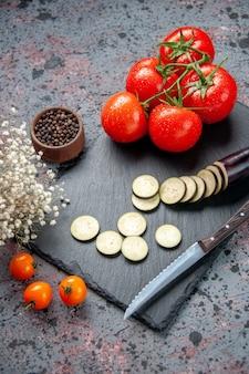 Вид спереди черные баклажаны со свежими красными помидорами на синем фоне