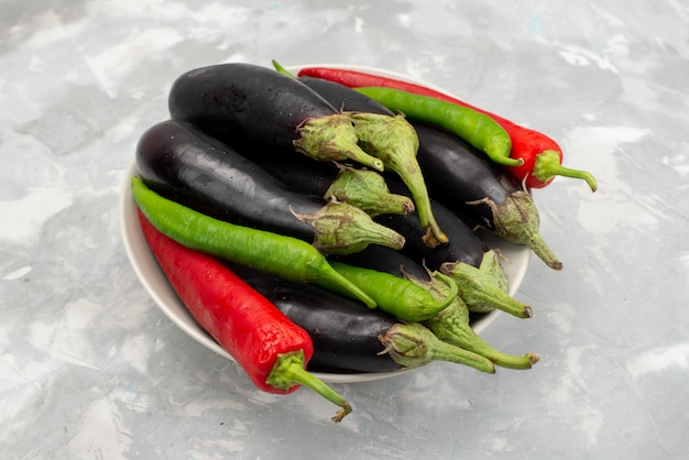Front view of black eggplants with peppers on the light desk