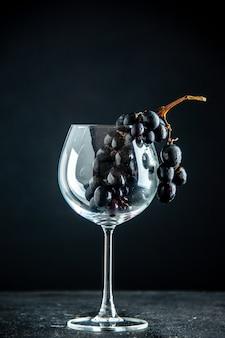 Vista frontale dell'uva nera in un bicchiere di vino sullo spazio libero del tavolo nero