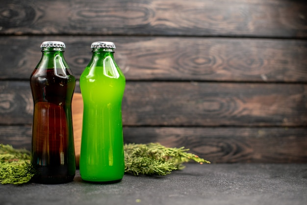 Vista frontale succhi neri e verdi in bottiglie rami di pino su tavola di legno