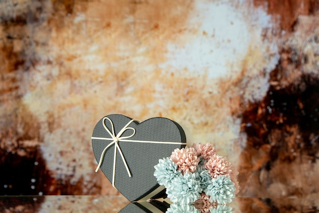 Front view of black heart box colored flowers on brown abstract background copy place