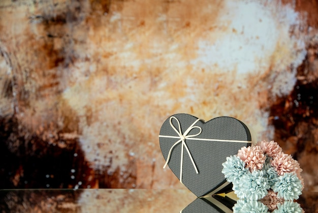 Front view of black heart box colored flowers on brown abstract background