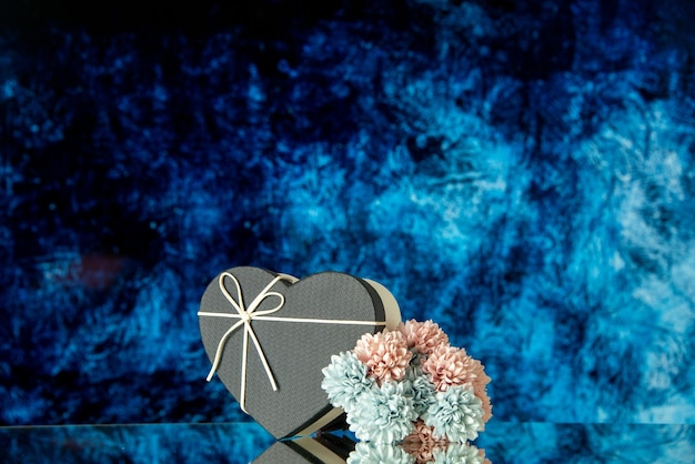 Vista frontale di fiori colorati scatola cuore nero su sfondo astratto blu scuro