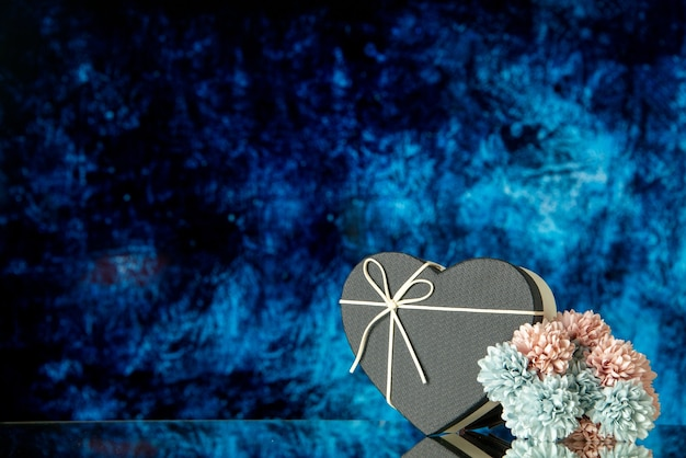 Front view of black heart box colored flowers on dark blue abstract background