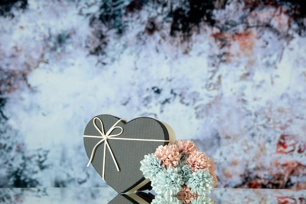 Vista frontale di fiori colorati scatola cuore nero su sfondo astratto grigio scuro