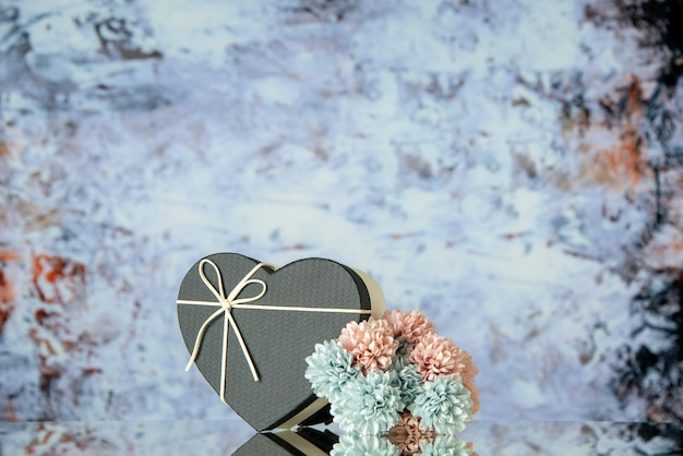 Front view of black heart box colored flowers on grey abstract background with free space