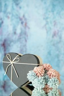 Vista frontale dei fiori colorati scatola a forma di cuore nero sul posto copia blu