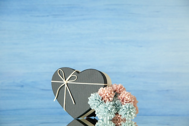 Front view of black heart shaped box colored flowers on blue with copy place